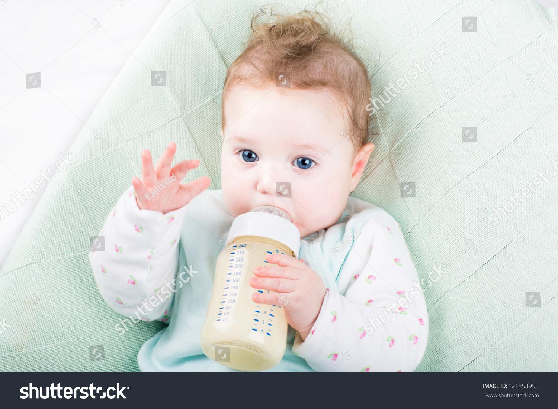 可爱的小女孩在一个绿色的针织毯子喝牛奶-食品及
