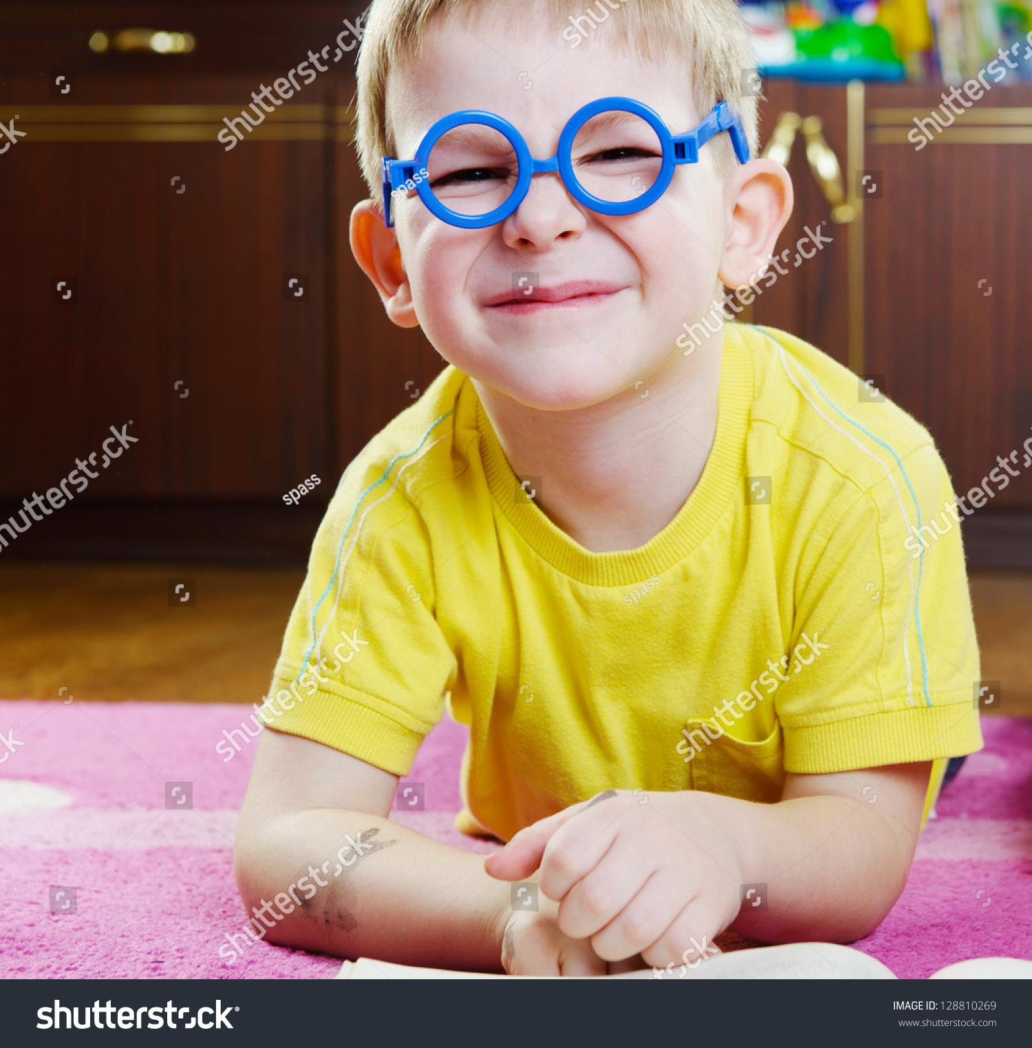 有趣的小男孩在眼镜躺在地板上-教育