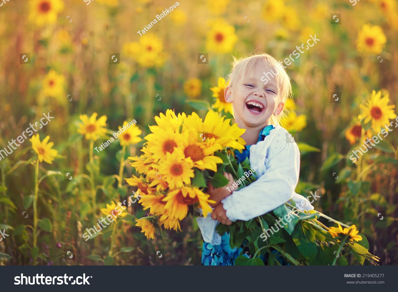 笑一个可爱的小女孩在向日葵抱着一大束花在一个阳光