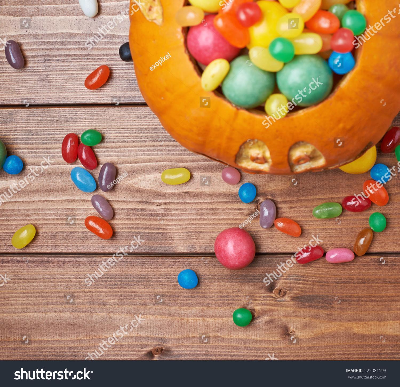 杰克o万圣节南瓜灯笼满多五颜六色的糖果,糖果木板背景组成,顶视图节