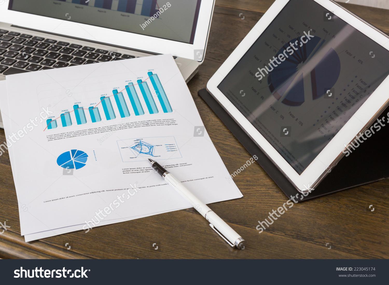 财务图表与平板电脑和笔记本电脑在桌子上