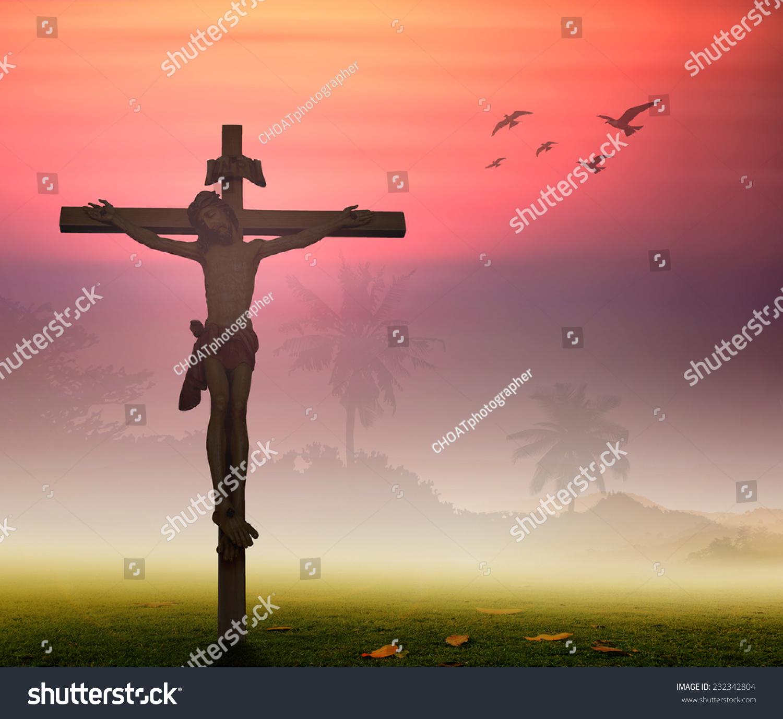 白色的十字架上耶稣基督在日落的背景