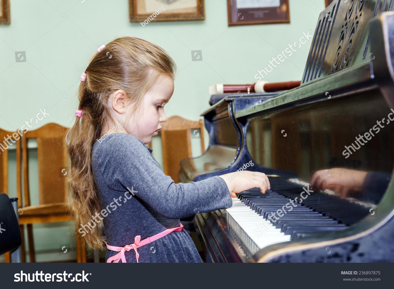 可爱的小女孩玩钢琴在音乐学校