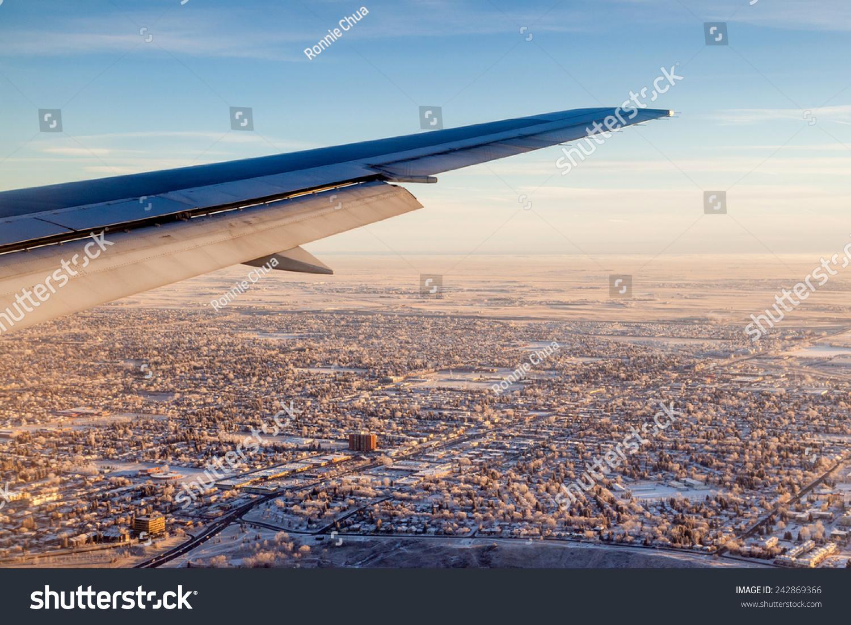 飞机窗口视图显示机翼的飞机飞过白雪覆盖的城市卡尔