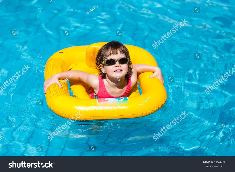 可爱的小女孩在游泳池里游泳在一个黄色的生命线