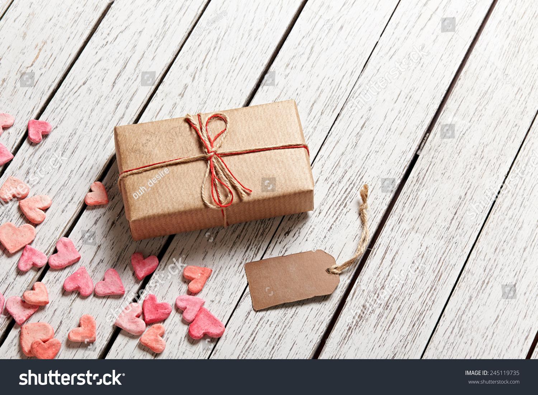 葡萄酒礼盒空白礼物标签和堆的小心脏在白色木制背景