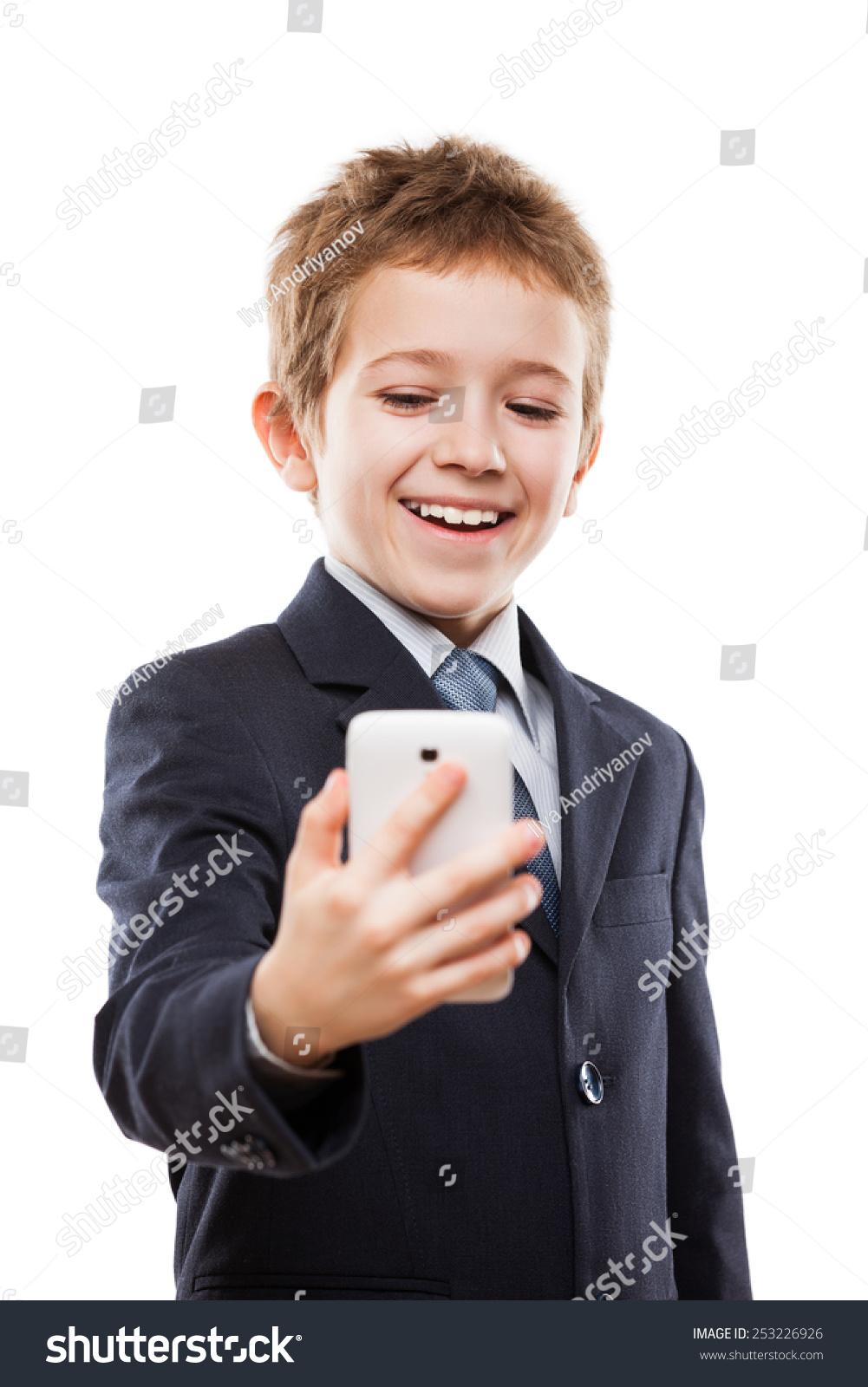 微笑的孩子小男孩在西装牵手手机或智能手机有问题的