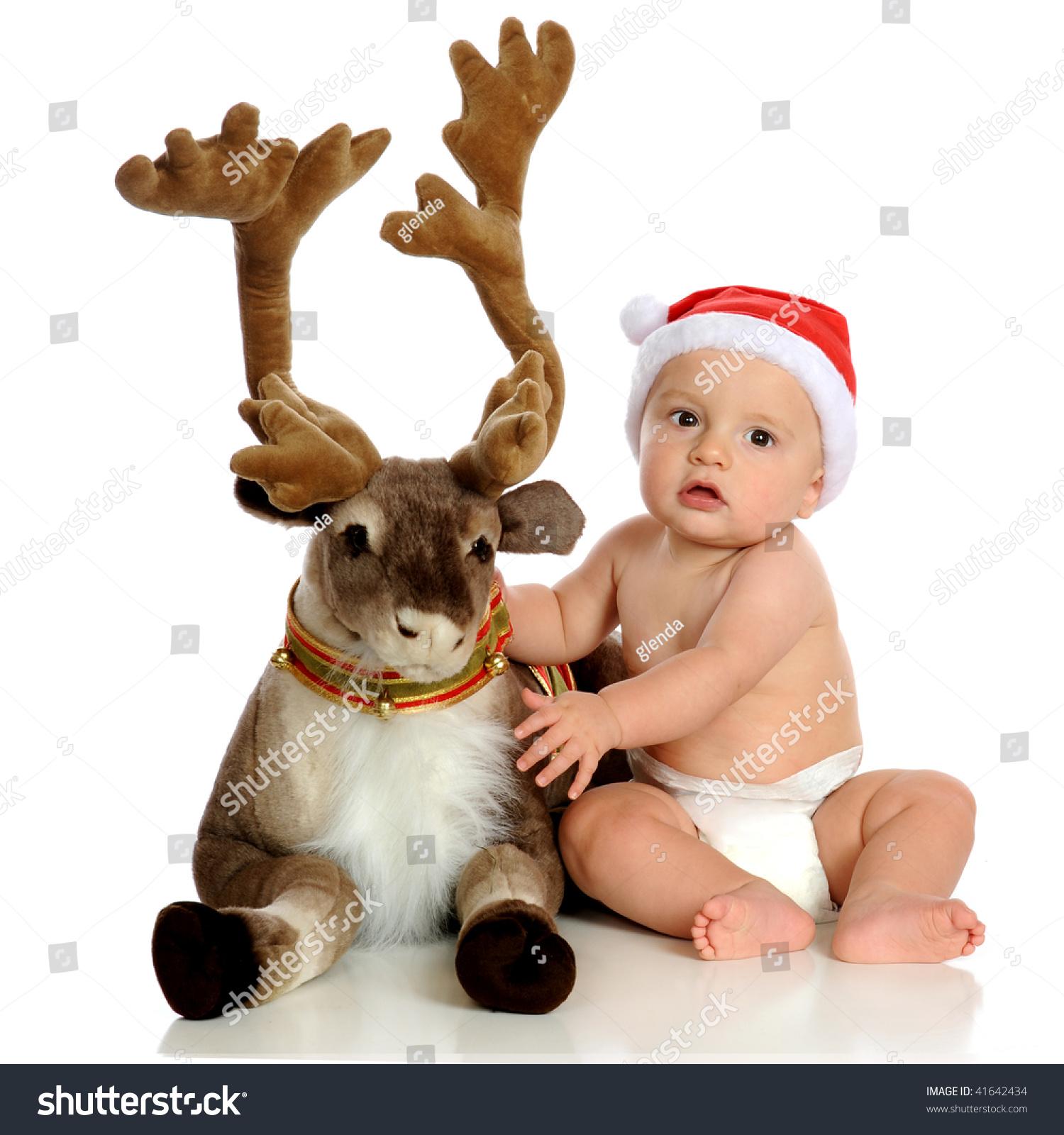 一个可爱的宝宝穿着圣诞老人的帽子与豪华的驯鹿